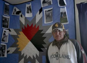 Ed Quiver, 48, stands in front of a quilt with photos of his grandchildren hanging on it in his room at Karluk Manor on Thursday, August 20, 2015.